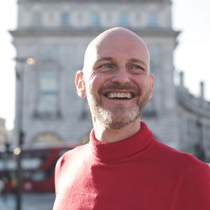Portrait of a man walking in the street and laughing a lot - Businessman standing in the middle of Piccadilly Circus, London - Bald man wearing a red turtleneck